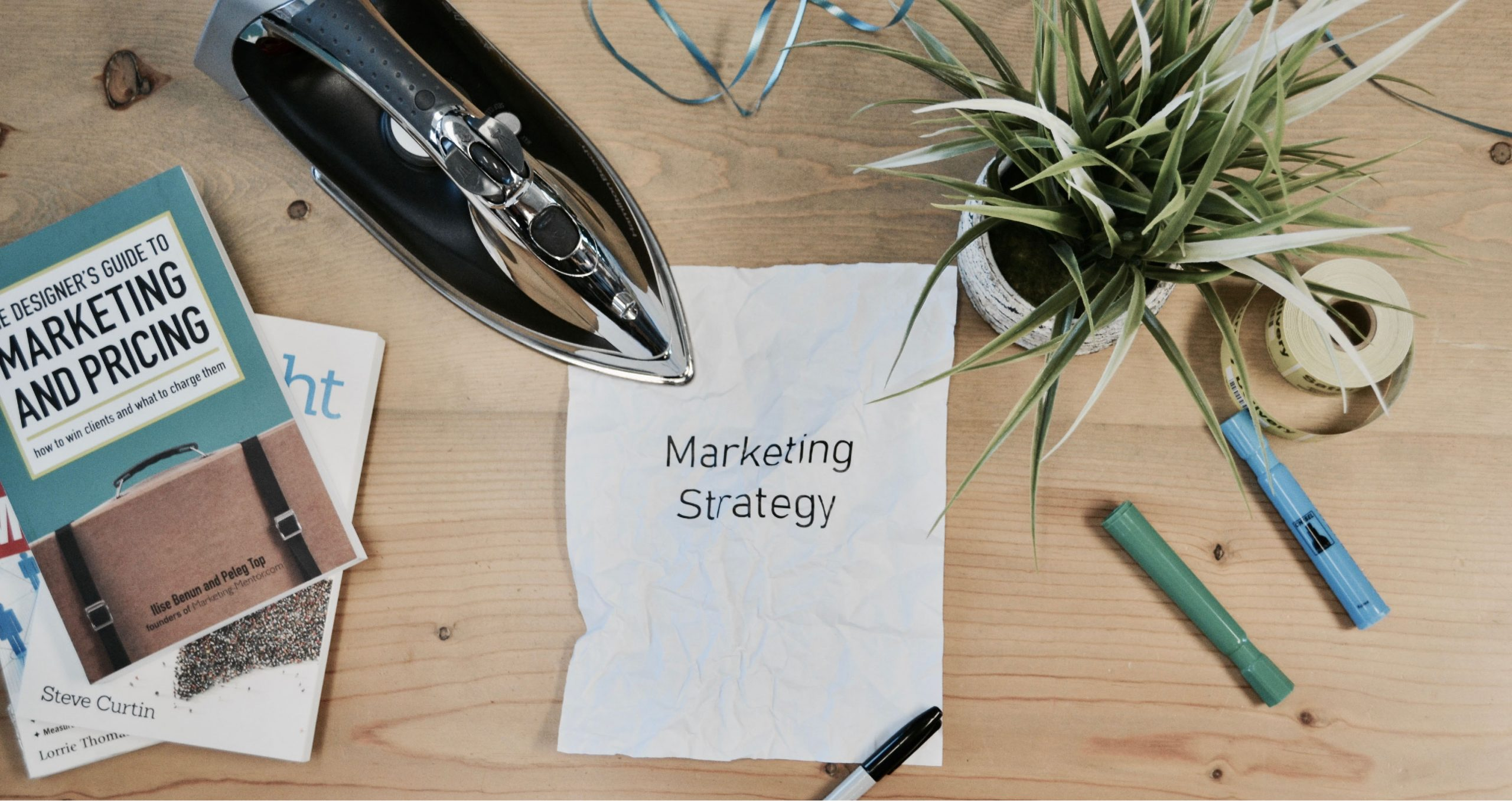 A photo of a paper that says Marketing Strategy with an iron next to it
