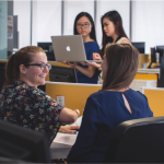 A photo of an open concept office environment with two women speaking to eachtoher