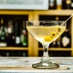 A photo of a martini with olives