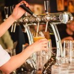 A photo of a bartender pouring a beer from a tap