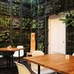 A photo of a corner at a restaurant surrounded by walls with plants