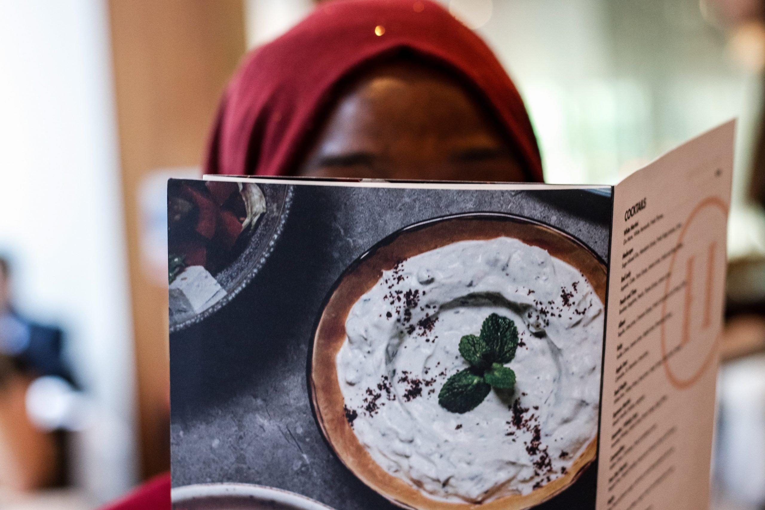 A photo of a woman looking at a menu