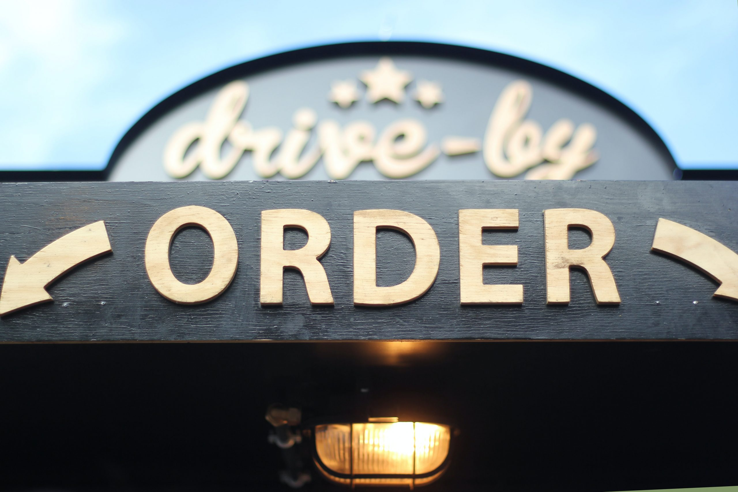 A photo of a sign that says Drive-By and Order