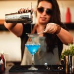 A photo of a bartender pouring a cocktail in a martini glass