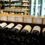 A photo of bottles of wine laying down at a store.