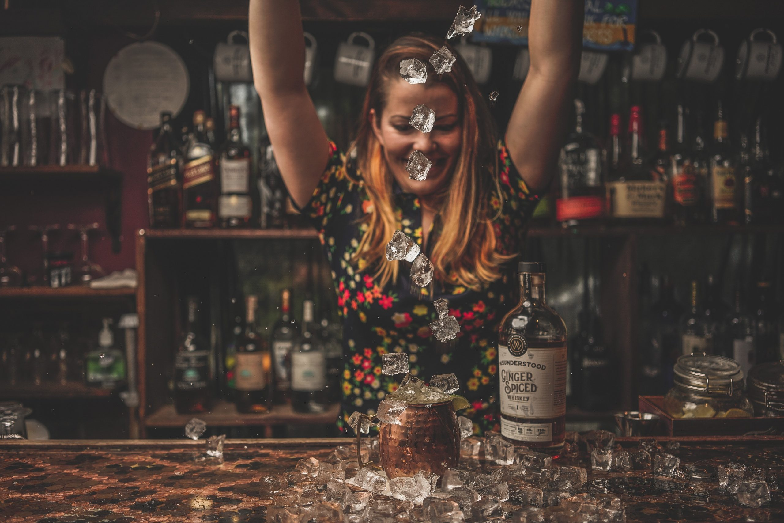 A photo of a woman throwing ice while making a Ginger cocktail.