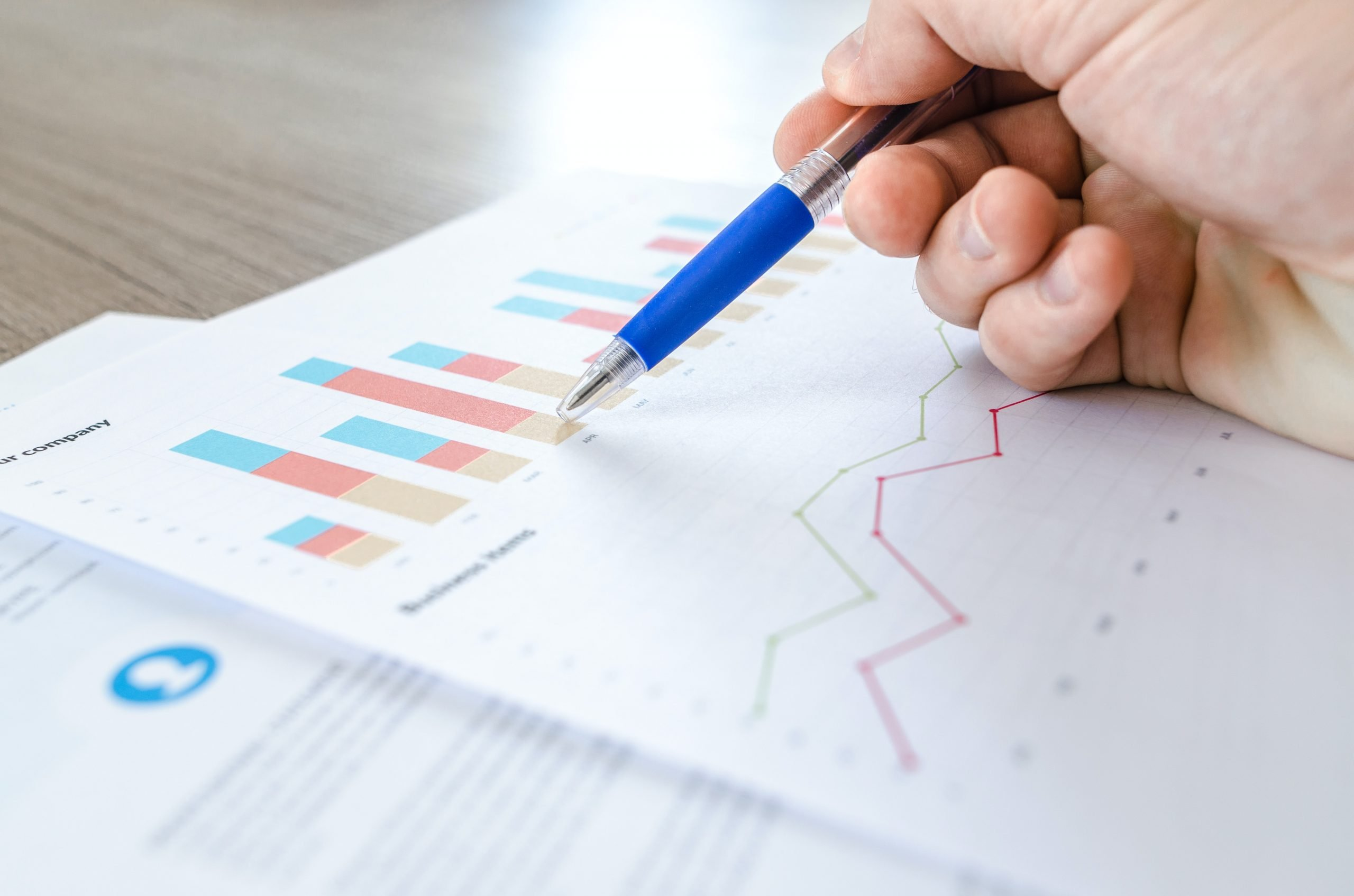 A photo of a hand using a pen while pointing at a printout of charts.