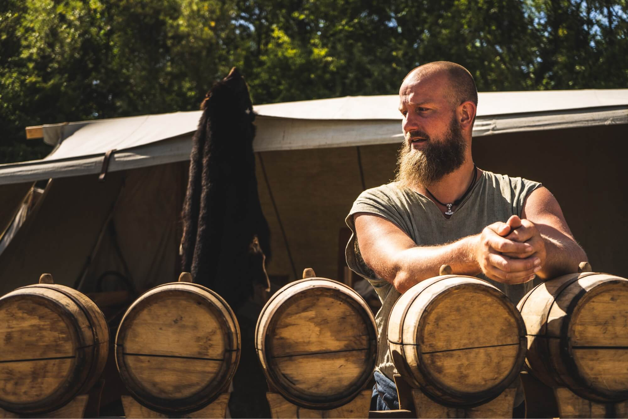A photo of a man leaning on whiskey barrels.