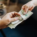 A photo of two people exchanging money.