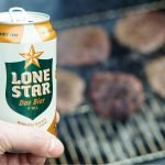 A photo of a hand holding Lone Star beer.