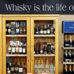 """A photo with whiskey bottles on shelves and a sign that says """"Whisky is the life of man"""""""