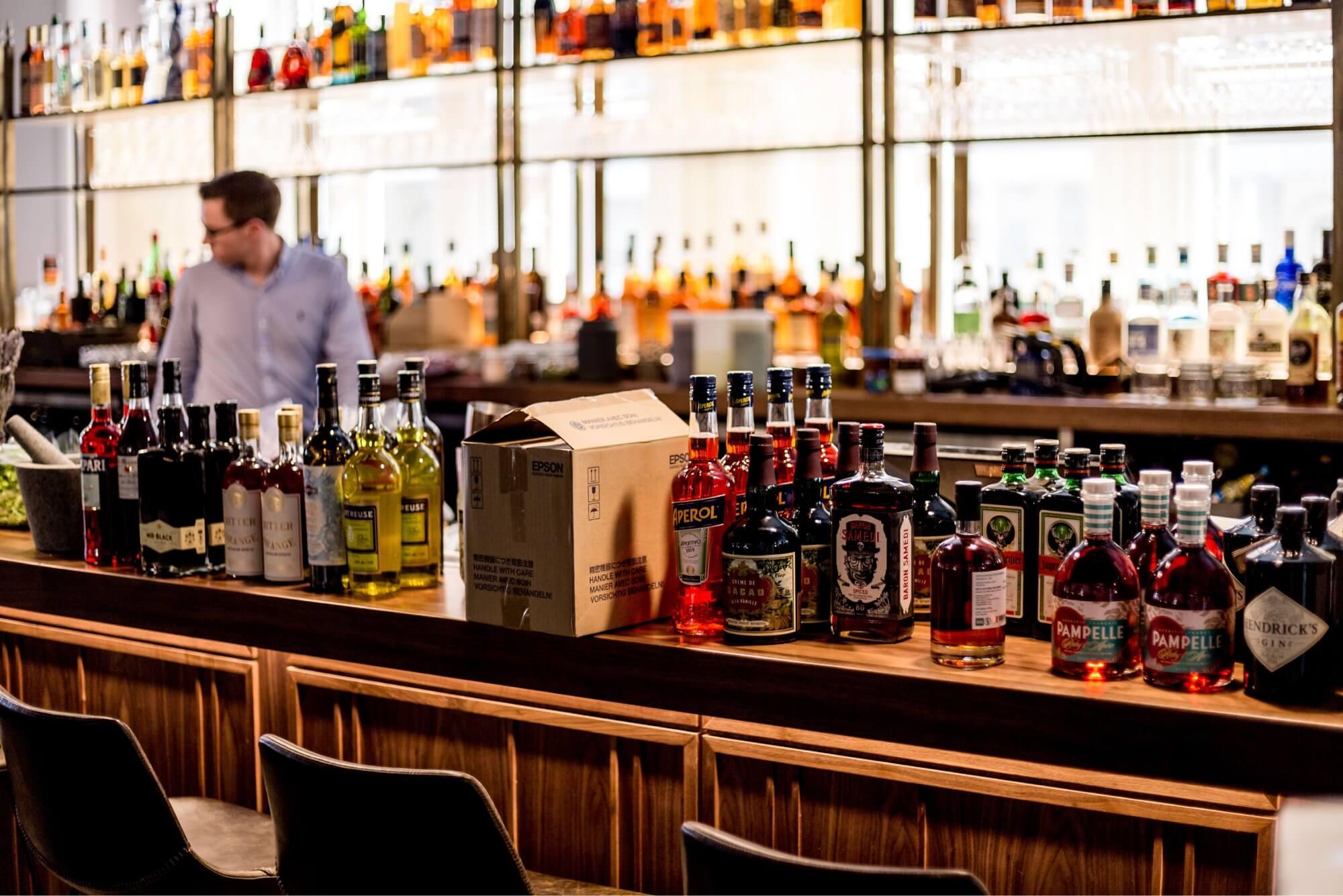 A photo of liquor bottles on a bar.
