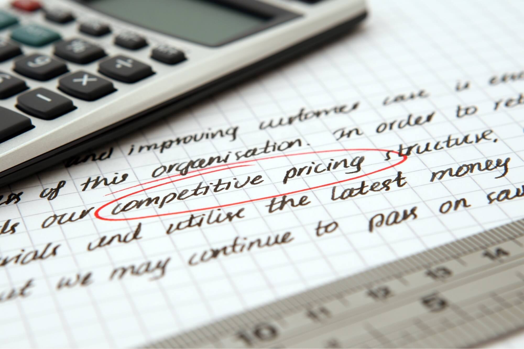 A photo of writing on a piece of paper with the words competitive pricing circled.