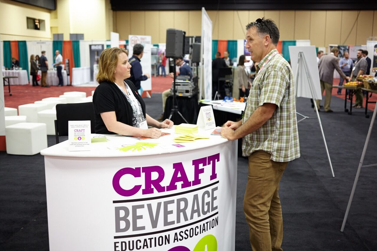 A photo of a man and woman engaging at a trade show.